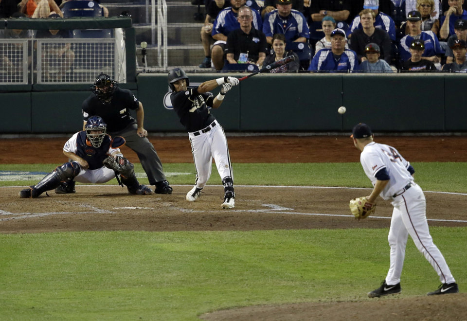 Photo - Vanderbilt shortstop Vince Conde follows though on an RBI single against Virginia in the sixth inning of Game 3 of the best-of-three NCAA baseball College World Series finals, in Omaha, Neb., Wednesday, June 25, 2014. (AP Photo/Nati Harnik)