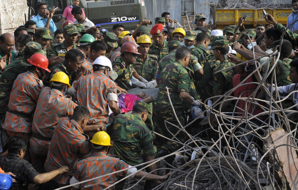Photo - Rescuers carry a survivor pulled out from the rubble of a building that collapsed in Saver, near Dhaka, Bangladesh, Friday, May 10, 2013. Rescue workers in Bangladesh freed the woman buried for 17 days inside the wreckage of a garment factory building that collapsed, killing more than 1,000 people. Soldiers at the site said her name was Reshma and described her as being in remarkably good shape despite her ordeal. (AP Photo/Rahul Talukder)