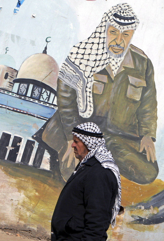 An elderly Palestinian walks next to a mural depicting Yasser Arafat, in the northern West Bank village of Kabatyeh, Monday, Nov. 26, 2012. The remains of former Palestinian leader Yasser Arafat were exhumed on Tuesday, Nov. 27, 2012, as part of a renewed investigation into his death, a Palestinian investigator said. (AP Photo/Mohammed Ballas)