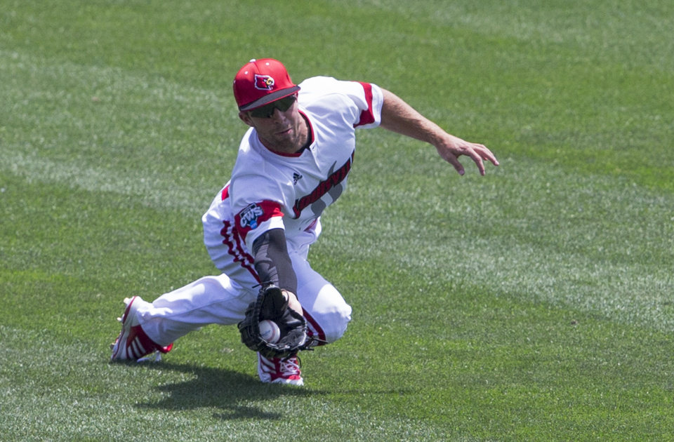 Photo - Louisville center fielder Cole Sturgeon catches a fly ball hit by Texas' Brooks Marlow in the first inning of an NCAA baseball College World Series elimination game, Monday, June 16, 2014, in Omaha, Neb. (AP Photo/Nati Harnik)
