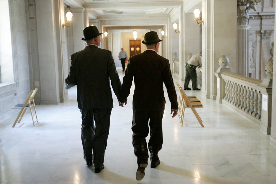 Photo - In this file photo from Tuesday, June 17, 2008, Curt Garman, left, and Richard Looke hold hands as they look for a quiet spot to hold their wedding at City Hall in San Francisco. The U.S. Supreme Court decided Friday, Dec. 7, 2012, to hear the appeal of a ruling that struck down Proposition 8, the state's measure that banned same sex marriages. The highly anticipated decision by the court means same-sex marriages will not resume in California any time soon. The justices likely will not issue a ruling until spring of next year. A federal appeals court ruled in February that Proposition 8's ban on same-sex marriage was unconstitutional. But the court delayed implementing the order until same-sex marriage opponents proponents could ask the U.S. Supreme Court to review the ruling. (AP Photo/Marcio Jose Sanchez)