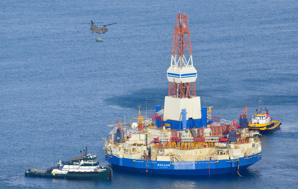 Photo - This aerial photo shows a U.S. Army CH-47 Chinook helicopter sling a trailer aboard the Shell floating drill rig in Kodiak Island, Alaska's Kiliuda Bay on Monday afternoon, Jan. 7, 2013, as salvage teams conduct an in-depth assessment of its seaworthiness. The Kulluk, which ran aground a week ago on Sitkalidak Island near Kodiak, was taken to Kiliuda Bay for repairs and a survey. (AP Photo/Kodiak Daily Mirror, James Brooks)