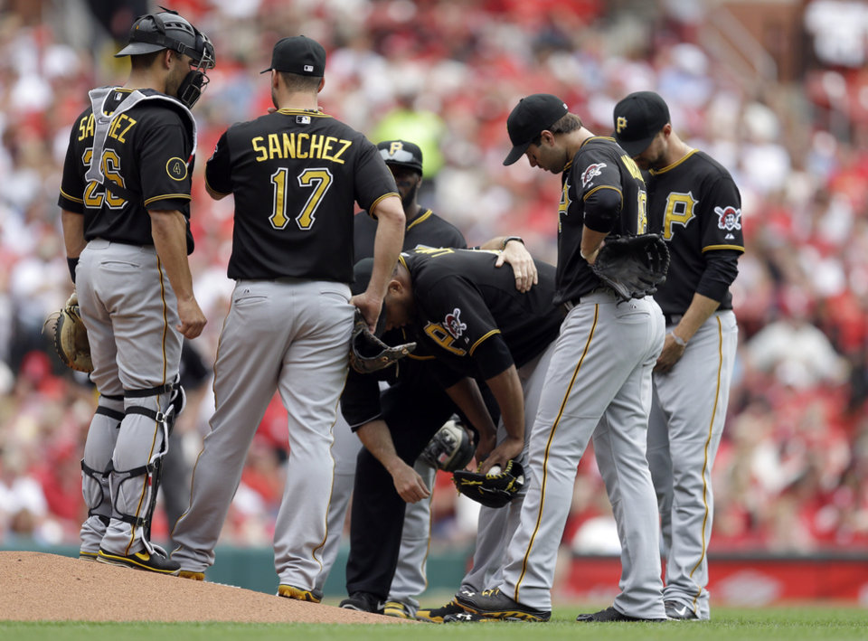 Photo - Pittsburgh Pirates starting pitcher Francisco Liriano bends over as teammates gather around him during the third inning of a baseball game against the St. Louis Cardinals on Saturday, April 26, 2014, in St. Louis. Liriano left the game soon after. (AP Photo/Jeff Roberson)