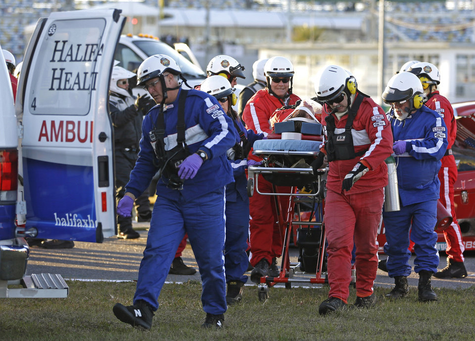 Photo - Rescue workers move driver Memo Gidley to an ambulance after he was involved in a crash at the IMSA Series Rolex 24 hour sports car race at Daytona International Speedway in Daytona Beach, Fla., Saturday, Jan. 25, 2014. (AP Photo/John Raoux)