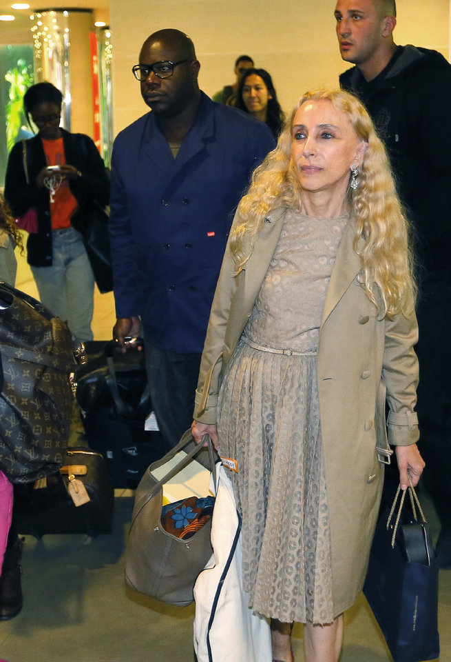 Photo - British film director and producer Steve McQueen, left, and Italian journalist and the editor-in-chief of Vogue Italia Franca Sozzani, right, foreground, arrive in Florence, Italy, Saturday, May 24, 2014. Kim Kardashian and Kanye West will wed and host a reception at Florence's imposing 16th-century Belvedere Fort on May 24, according to a spokeswoman at the Florence mayor's office. The couple rented the fort, located next to Florence's famed Boboli Gardens, for 300,000 euros ($410,000) and a Protestant minister will preside over the ceremony. Belvedere Fort was built in 1590, believed using plans by Don Giovanni de' Medici. Located near the Arno River, it offers a panoramic view of Florence and the surrounding Tuscan hills. (AP Photo/Fabio Muzzi)