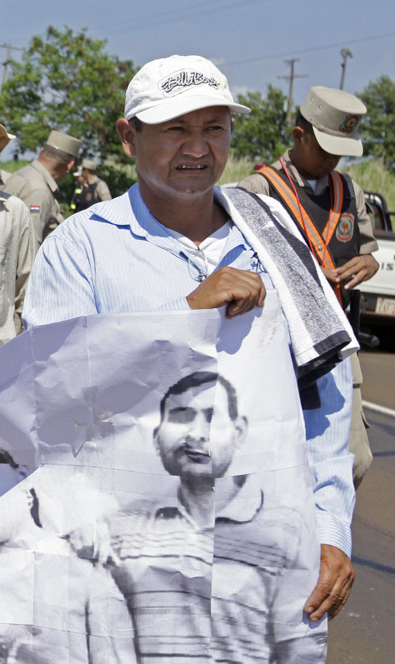 In this photo taken Nov. 15 2012 Vidal Vega, left,  holds a banner during a march to demand the freedom of landless farmers near Curuguaty city, Paraguay. Early Saturday gunmen murdered 48-year-old Vega, one of the surviving leaders of a peasant movement whose land dispute with a powerful politician prompted the end of Fernando Lugo's presidency last June.  He was hit four times by bullets from a 12-gauge shotgun and a .38-caliber revolver fired by two unidentified men at his house in the peasant settlement of  Yvy Pyta, in the outskirts of Curuguaty.(AP Photo/Jorge Saenz)