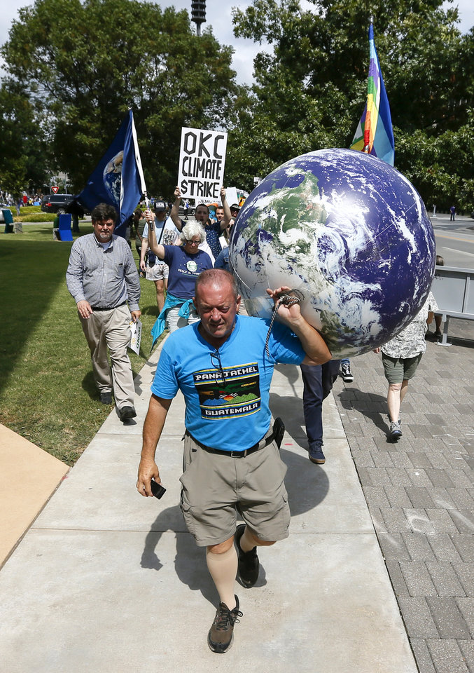 Photo - Richie Monarch carries an inflatable globe as people march south on Hudson Ave. away from City Hall during the Oklahoma City Climate Strike event, part of global rallies and marches to bring attention to climate change, in Oklahoma City, Friday, Sept. 20, 2019. [Nate Billings/The Oklahoman]