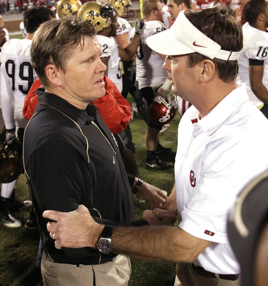 Photo - OU head coach Bob Stoops, right, and Colorado head coach Dan Hawkins shake hands after the  University of Oklahoma defeated the University of Colorado Buffaloes 43-10 at Gaylord Family-Oklahoma Memorial Stadium in Norman, Okla., Saturday, October 30, 2010.  Photo by Steve Sisney, The Oklahoman