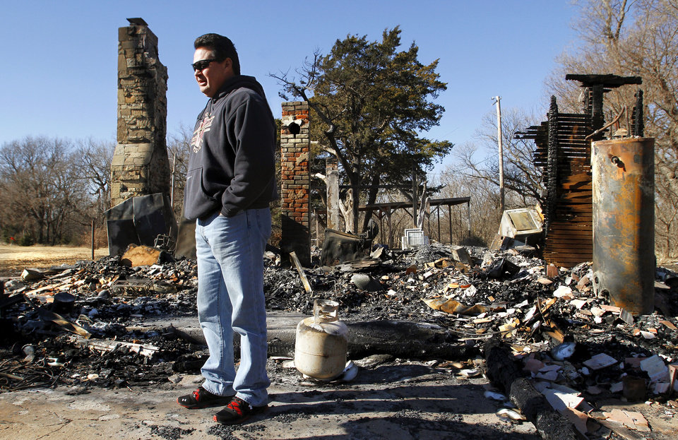 Chris Cochran stands among the charred rubble that was his  family's home in a rural area near Cashion until it was destroyed in a recent fire.  His son, Cayden Cochran, a star player when he attended Cashion High School, is now starting quarterback at Division II power Valdosta State, and this weekend, he leads Valdosta into the Division II national championship game. Photo taken Wednesday, Dec. 12, 2012.    Photo by Jim Beckel, The Oklahoman <strong>Jim Beckel - THE OKLAHOMAN</strong>