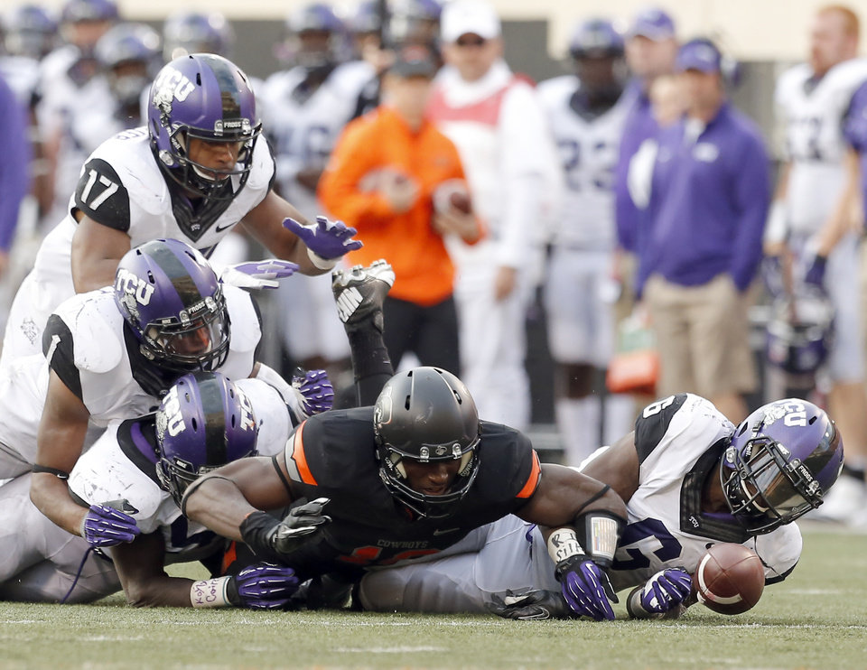 Photo - Oklahoma State's Blake Jackson (18) fumbles the ball as he tackled by a host of TCU players during a college football game between Oklahoma State University (OSU) and Texas Christian University (TCU) at Boone Pickens Stadium in Stillwater, Okla., Saturday, Oct. 27, 2012. Photo by Sarah Phipps, The Oklahoman