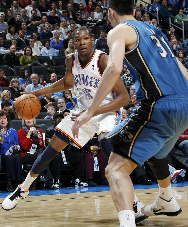 Oklahoma City's Kevin Durant (35) looks to drive the ball past Yi Jianlian (31) of Washington during the NBA basketball game between the Washington Wizards and the Oklahoma City Thunder at the Oklahoma City Arena in Oklahoma City, Friday, January 28, 2011. Photo by Nate Billings, The Oklahoman