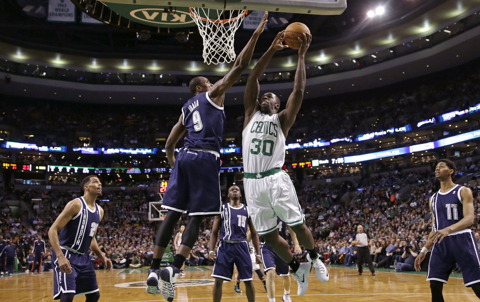 Photo - Boston Celtics forward Brandon Bass (30) drives to the basket against Oklahoma City Thunder forward Serge Ibaka (9) during the first half of an NBA basketball game in Boston, Friday, Jan. 24, 2014. (AP Photo/Charles Krupa)