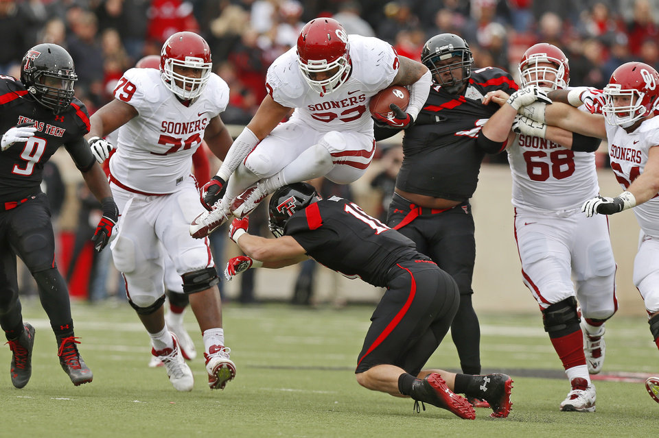 Photo - Oklahoma's Trey Millard (33) leaps over Texas Tech's Cody Davis (16) during a college football game between the University of Oklahoma (OU) and Texas Tech University at Jones AT&T Stadium in Lubbock, Texas, Saturday, Oct. 6, 2012. Photo by Bryan Terry, The Oklahoman