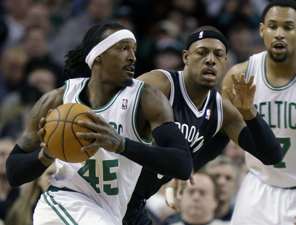 Photo - Boston Celtics forward Gerald Wallace (45), tries to drive past Brooklyn Nets forward Paul Pierce, center, in the first quarter of an NBA basketball game, Sunday, Jan. 26, 2014, in Boston. Celtics center Jared Sullinger looks on at right. (AP Photo/Steven Senne)