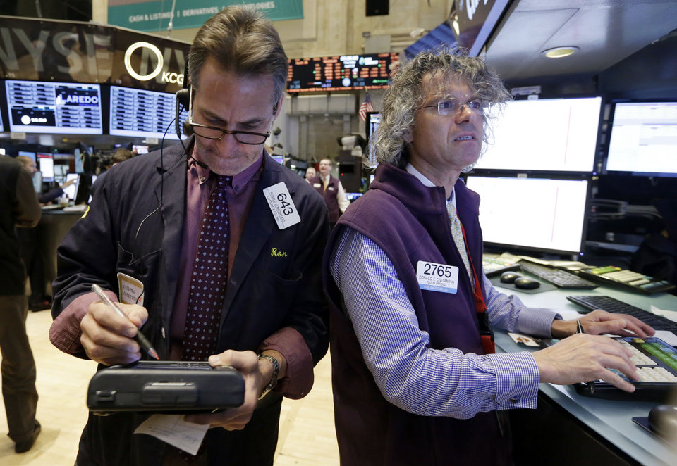 Photo - Trader Ronald Madarasz, left, and specialist Donald Civitanova work on the floor of the New York Stock Exchange Thursday, April 10, 2014.  U.S. stock indexes are slipping lower in early trading Thursday as investors pick over a mixed batch of corporate earnings reports. (AP Photo/Richard Drew)