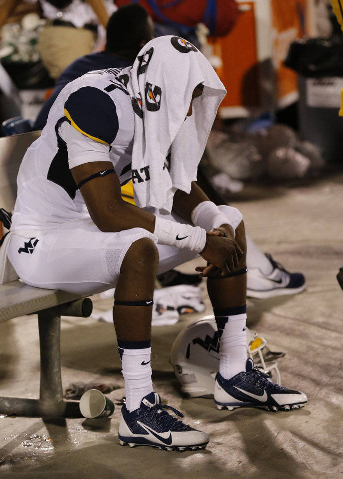 Photo - A West Virginia player sits dejected on the bench following a college football game between the University of Oklahoma Sooners (OU) and the West Virginia University Mountaineers at Gaylord Family-Oklahoma Memorial Stadium in Norman, Okla., on Saturday, Sept. 7, 2013. Photo by Steve Sisney, The Oklahoman