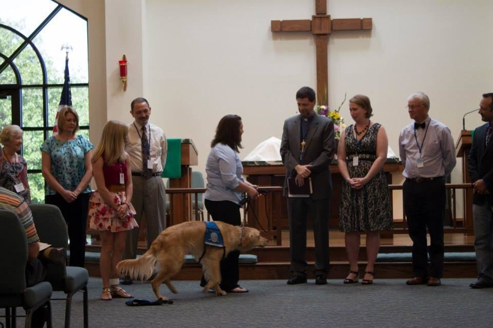 Photo -  Sherry Bolosan, with Lutheran Church Charities, formally passes Rufus Comfort Dog's leash to the Rev. Mark Erler and the congregation at St. Mark Lutheran Church in Edmond Photo by Mandy Long, for The Oklahoman