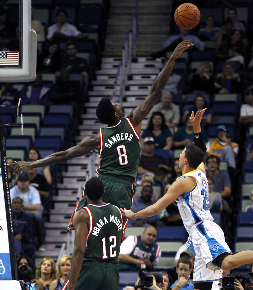 Photo - Milwaukee Bucks center Larry Sanders (8) blocks a shot by New Orleans Hornets guard Austin Rivers (25) in the first half of an NBA basketball game in New Orleans, Monday, Dec. 3, 2012. (AP Photo/Gerald Herbert)