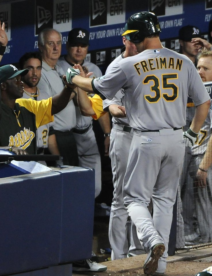 Photo - Oakland Athletics' Nate Freiman (35) is congratulated in the dugout after his solo home run against the Atlanta Braves during the seventh inning of a baseball game Sunday, Aug. 17, 2014, in Atlanta. (AP Photo/David Tulis)