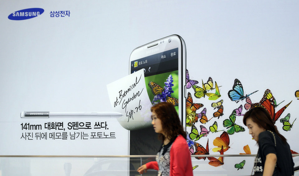 Visitors walk by a billboard of Samsung Electronics\'s product at a showroom of its headquarters in Seoul, South Korea, Friday, Oct. 5, 2012. Samsung Electronics Co. tipped all-time high quarterly operating profit, likely driven by strong sales of high-end smartphones that offset weak semiconductor orders. (AP Photo/Lee Jin-man)