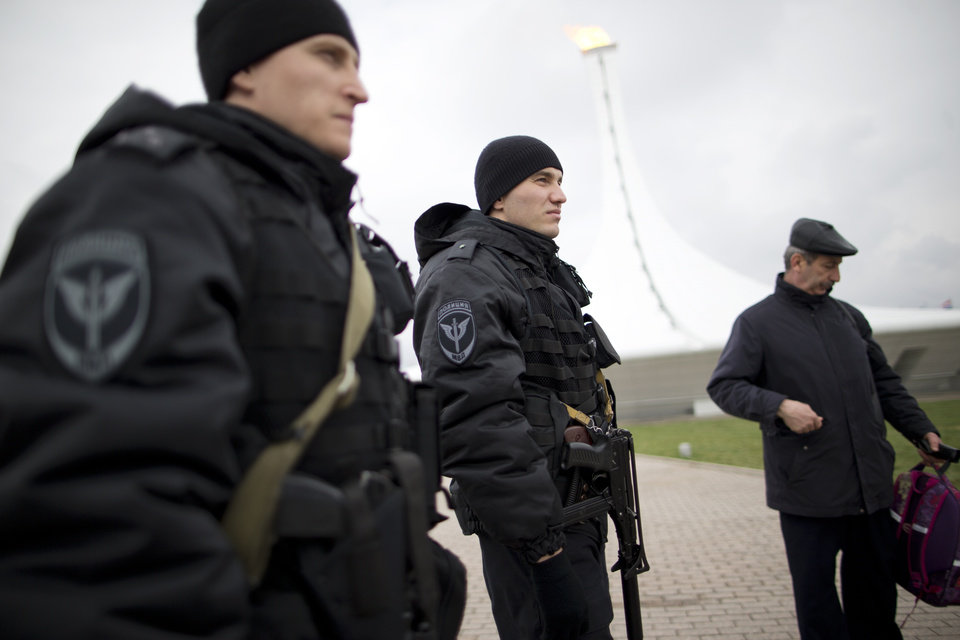 Photo - Russian special forces patrol Olympic Park near the Olympic Cauldron during the 2014 Winter Olympics, Monday, Feb. 17, 2014, in Sochi, Russia. Sochi hotel guests are walking, unchecked, past unused metal detectors. Security guards are no longer poking around at the pockets and ankles of every single person entering Olympic facilities. Tangerines and bottles of Coke are making it through security barriers that banned them two weeks ago. For all the warnings that security in Sochi would be invasive and aggressive, it's appearing more uneven, and in places almost relaxed.  (AP Photo/Pavel Golovkin)