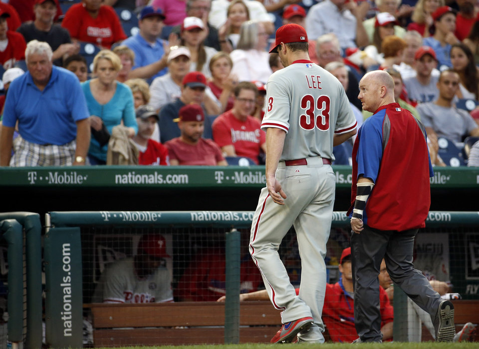 Photo - Philadelphia Phillies starting pitcher Cliff Lee (33) walks to the dugout during the third inning of a baseball game against the Washington Nationals at Nationals Park Thursday, July 31, 2014, in Washington. The Phillies announced that Lee had a recurrence of the left flexor pronator strain that sidelined him in May. (AP Photo/Alex Brandon)