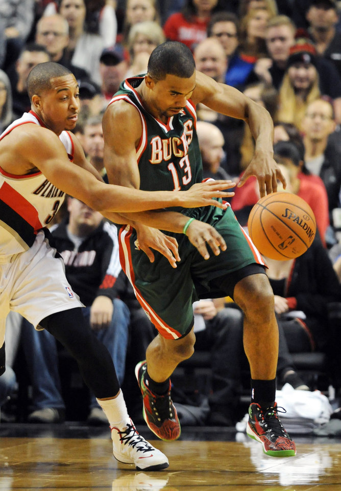 Photo - Portland Trail Blazers guard C.J. McCollum (3) tries to knock the ball away from Milwaukee Bucks guard Ramon Sessions (13) during the first half of an NBA basketball game in Portland, Ore., Tuesday, March 18, 2014. (AP Photo/Steve Dykes)