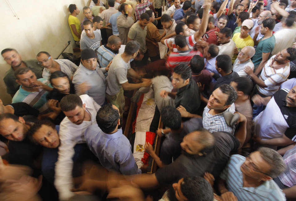 Photo - Supporters of Egypt's ousted President Mohammed Morsi surround a coffin, covered with national flags, of their colleague who was killed during Wednesday' clashes in Amr Ibn Al-As mosque before a funeral prayers in Cairo, Egypt, Friday, Aug. 16, 2013. Gunfire rang out over a main Cairo overpass and police fired tear gas as clashes broke out after tens of thousands of Muslim Brotherhood supporters took to the streets Friday across Egypt in defiance of a military-imposed state of emergency following the country's bloodshed earlier this week. (AP Photo/Amr Nabil)