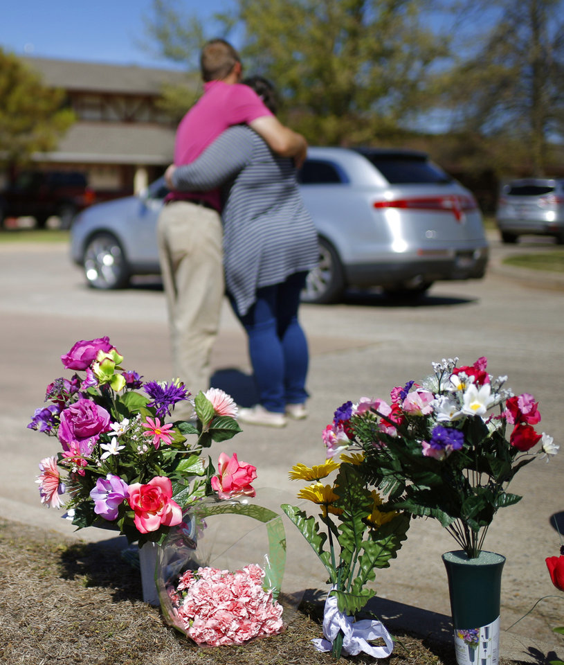 Photo -  Neighbors hug after placing flowers near the home of Cecille Short. [Photo by Bryan Terry, The Oklahoman]