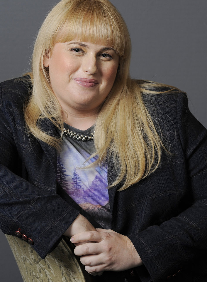 "FILE - In this Thursday, Aug. 23, 2012 file photo, actress, writer and comedienne Rebel Wilson, a cast member in the film ""Bachelorette,"" poses for a portrait at the Four Seasons Hotel in Beverly Hills, Calif. Wilson sings, dances and summons laughs _ and that's just in the opening moments of the upcoming MTV Movie Awards, on Sunday, April 14, 2013. The Australian actress is hosting the show, and she's set to start the ceremony by singing solo. (Photo by Chris Pizzello/Invision/AP, File)"