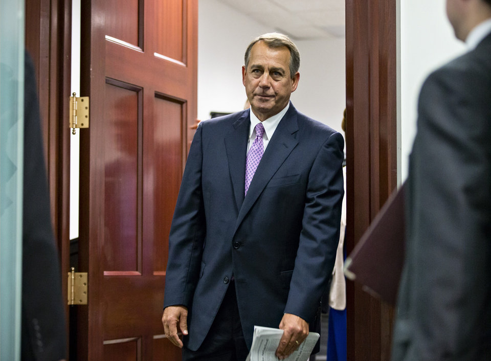Photo - House Speaker John Boehner of Ohio and other members of the Republican Caucus emerge from a closed-door strategy session on Capitol Hill in Washington, Friday, Oct. 4, 2013. Boehner is struggling between Democrats that control the Senate and GOP conservatives in his caucus who insist any funding legislation must also kill or delay the nation's new health care law. Added pressure came from President Barack Obama who pointedly blamed Boehner on Thursday for keeping federal agencies closed. (AP Photo/J. Scott Applewhite)