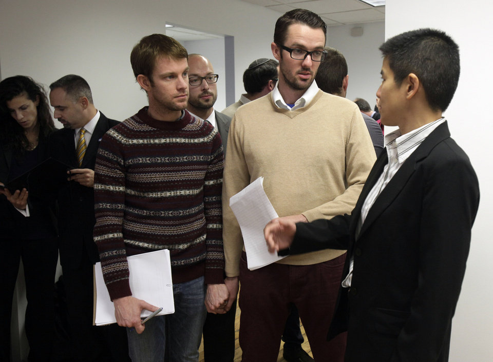 Photo -   Christine Sun, right, deputy legal director for the Southern Poverty Law Center, confers with Michael Ferguson, second right, and his partner Seth Anderson, before a news conference, in New York, Tuesday, Nov. 27, 2012. Ferguson, of Salt Lake City, is one of four gay men accusing a New Jersey organization of selling