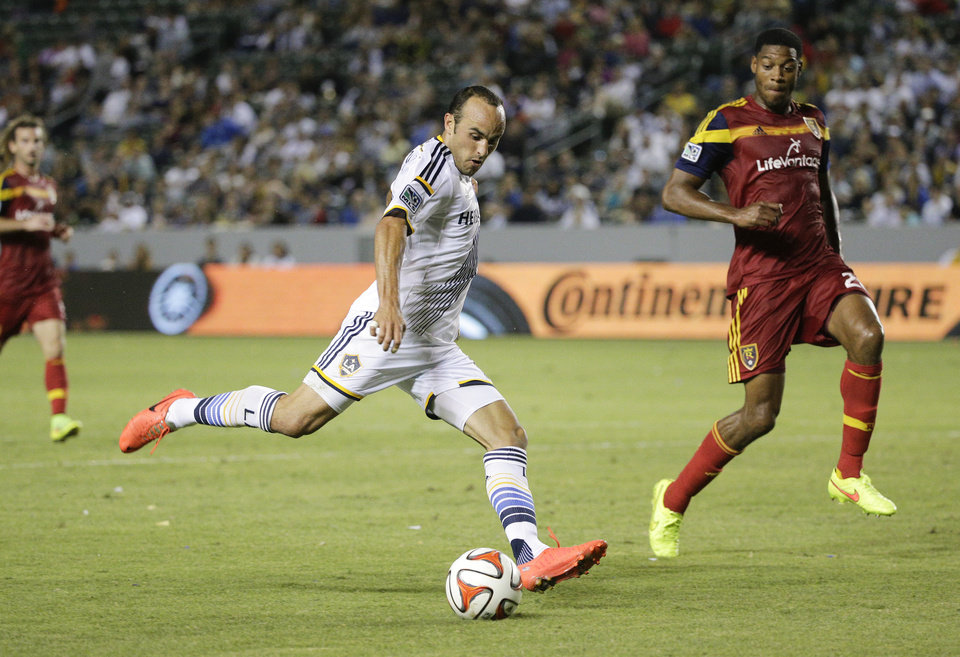 Photo - In this Saturday, July 12, 2014, photo, Los Angeles Galaxy's Landon Donovan, center, shoots as he is defended by Real Salt Lake's Chris Schuler during the second half of their MLS soccer match in Carson, Calif. Donovan says he will retire from professional soccer at the end of the MLS season. (AP Photo/Jae C. Hong)