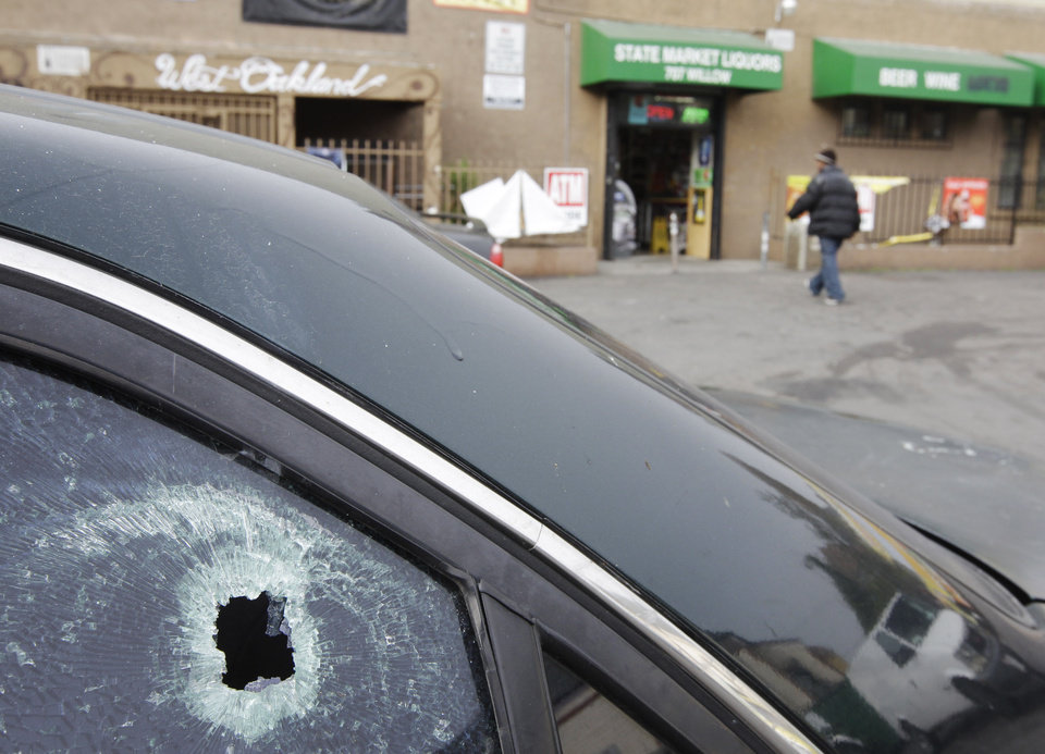 Photo - FILE - This Nov. 29, 2011 file photo shows a bullet hole in a window of a car at a liquor store parking lot in Oakland, Calif., after a shooting. A hail of gunfire along the Oakland street left eight people wounded, including a 1-year-old boy. In the wake of the Dec. 14, 2012 mass shooting at Sandy Hook Elementary School in the small town of Newtown, Conn., there is now much political discussion about gun control. For urban advocates, this new emphasis on gun control is long overdue. (AP Photo/Paul Sakuma, File)