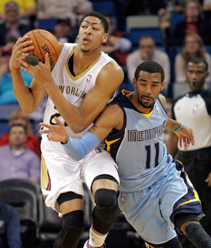 Photo - New Orleans Pelicans forward Anthony Davis (23) and Memphis Grizzlies guard Mike Conley (11) battle for the loose ball in the first half of an NBA basketball game, Wednesday, March 12, 2014, in New Orleans. (AP Photo/Scott Threlkeld)