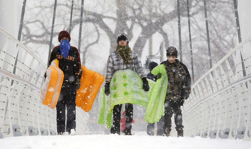 Chance Cain, from left, Simon Mourning and Nathan Talley walk towards a sledding hill near downtown Wichita, Kan. as a winter storm moves through the area on Monday, Feb. 25, 2013. (AP Photo/The Wichita Eagle, Travis Heying) LOCAL TV OUT; MAGS OUT; LOCAL RADIO OUT; LOCAL INTERNET OUT