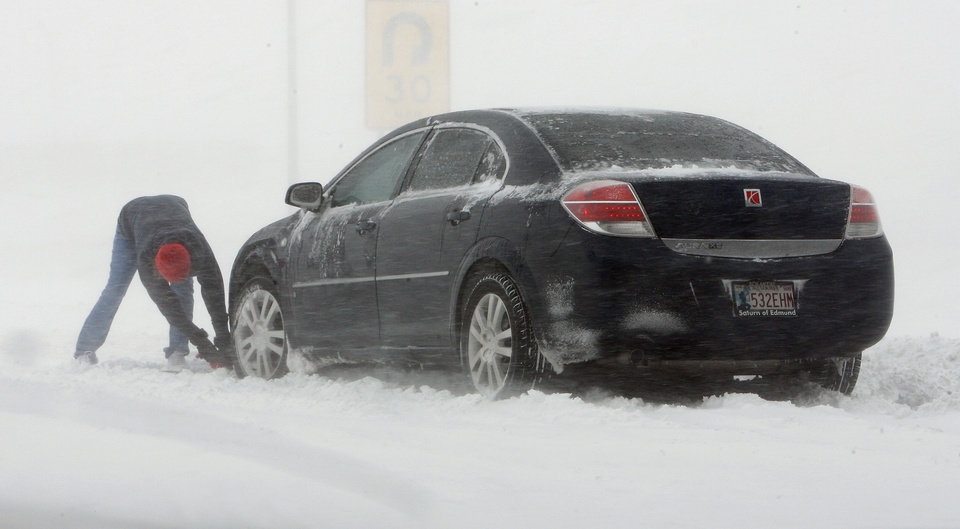 Photo - A motorist tries to free their car stuck in a snow drift in the southbound lanes of SH 81 just south of I-40 in El Reno Thursday, Dec. 24, 2009. I-40 is closed due to blizzard conditions. Photo by Paul B. Southerland, The Oklahoman
