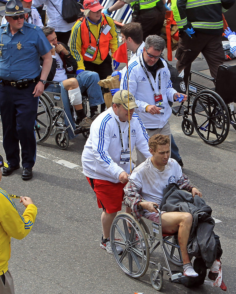 Workers aid injured people at the finish line of the 2013 Boston Marathon following an explosion in Boston, Monday, April 15, 2013. Two explosions shattered the euphoria of the Boston Marathon finish line on Monday, sending authorities out on the course to carry off the injured while the stragglers were rerouted away from the smoking site of the blasts. (AP Photo/The Boston Herald, Stuart Cahill) MANDATORY CREDIT ORG XMIT: MABOH801