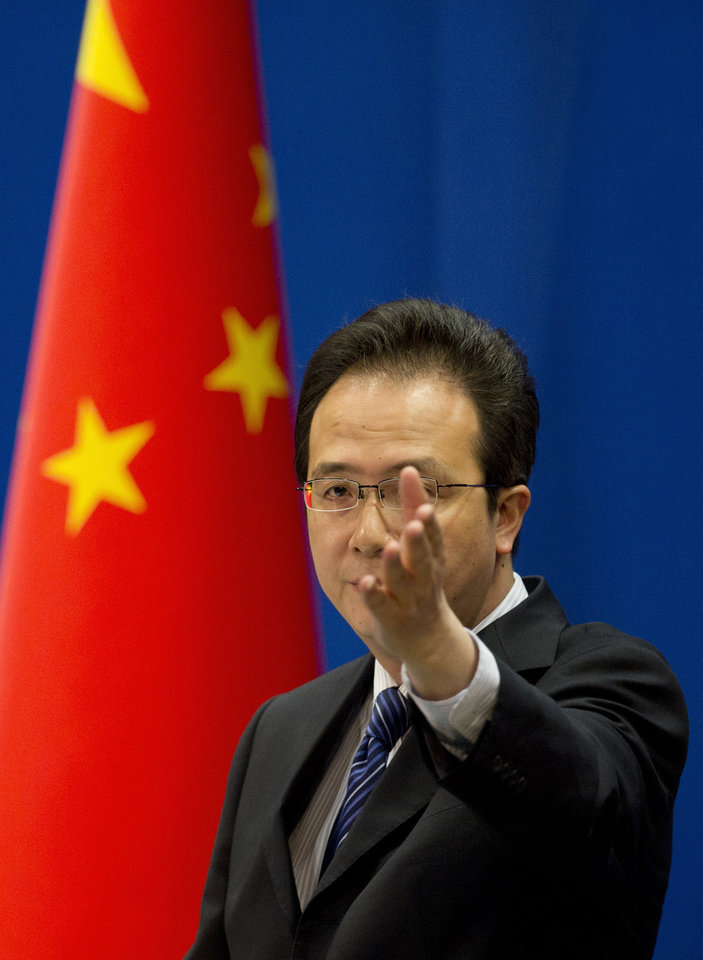 Photo - Foreign ministry spokesman Hong Lei gestures during a daily briefing at the Ministry of Foreign Affairs office in Beijing, China Tuesday, May 20, 2014. China on Tuesday warned the United States was jeopardizing military ties by charging five Chinese officers with cyberspying and tried to turn the tables on Washington by calling it