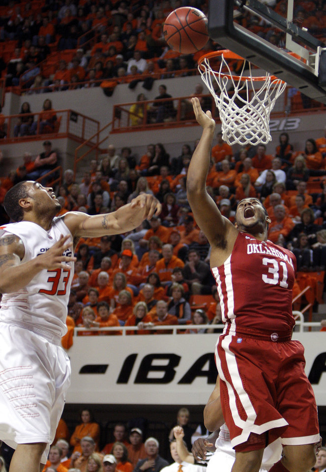 Photo - Oklahoma's Barry Honore (31) tips a ball for a basket as Oklahoma State's Marshall Moses (33)Êdefends during the Bedlam men's college basketball game between the University of Oklahoma Sooners and Oklahoma State University Cowboys at Gallagher-Iba Arena in Stillwater, Okla., Saturday, February, 5, 2011. Photo by Sarah Phipps, The Oklahoman