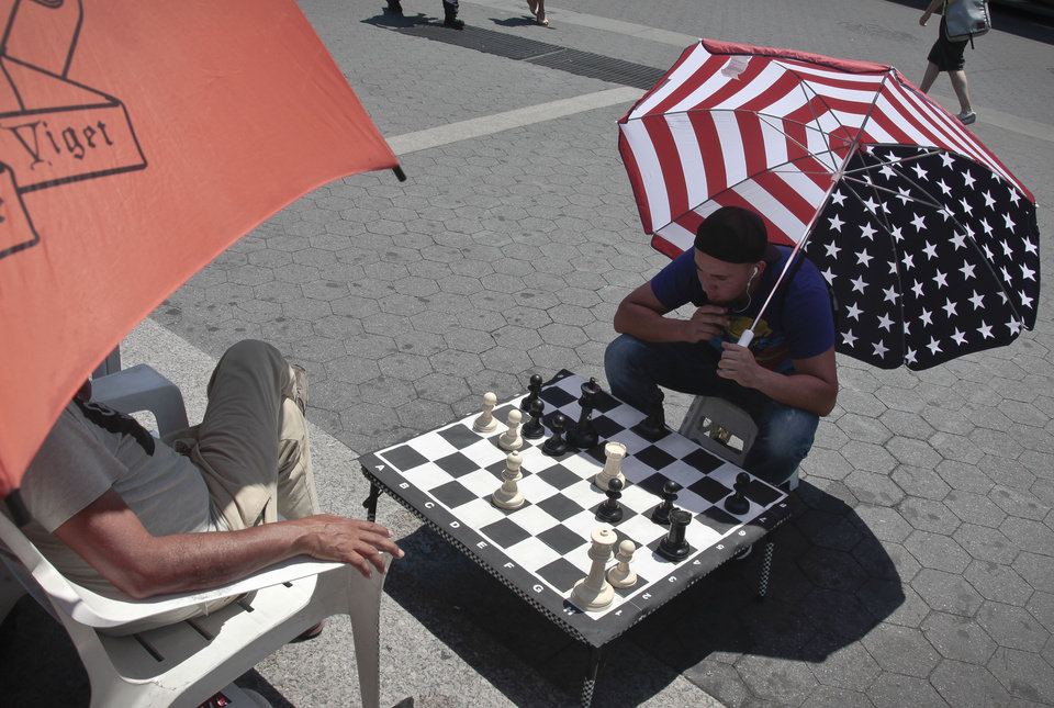 Photo -   Luis Saavevra shades from the heat with a giant U.S. flag umbrella as he plays chess on an over-sized board in Union Square as temperature reached the 90s on Friday, July 6, 2012 in New York. he National Weather Service reported late Thursday that the record-breaking heat that has baked the nation's midsection for several days was slowly moving into the mid-Atlantic states and Northeast. (AP Photo/Bebeto Matthews)