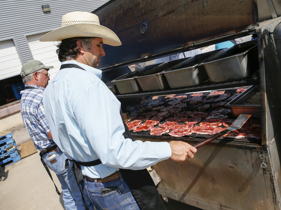 Photo -  Jeff Hammonds with the Oklahoma Cattlemen's Association, right, grills rib-eye steaks alongside Byron Yeoman with the Oklahoma Beef Council and the Oklahoma Cattlemen's Association at the Homeless Alliance's WestTown day shelter. [Photo by Nate Billings, The Oklahoman]