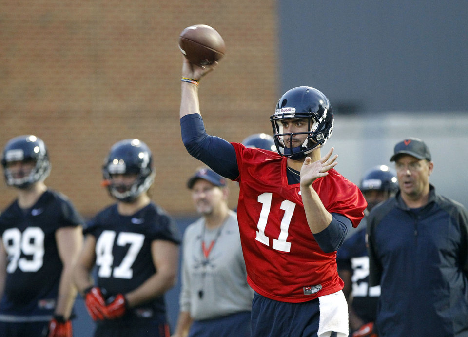Photo - Virginia quarterback Greyson Lambert (11) throws a pass during the first fall football practice on Monday, Aug. 25, 2014 in Charlottesville, Va.   The redshirt sophomore quarterback is preparing for the first start of his college career on Saturday against No. 7 UCLA.    (AP Photo/The Daily Progress, Ryan M. Kelly)