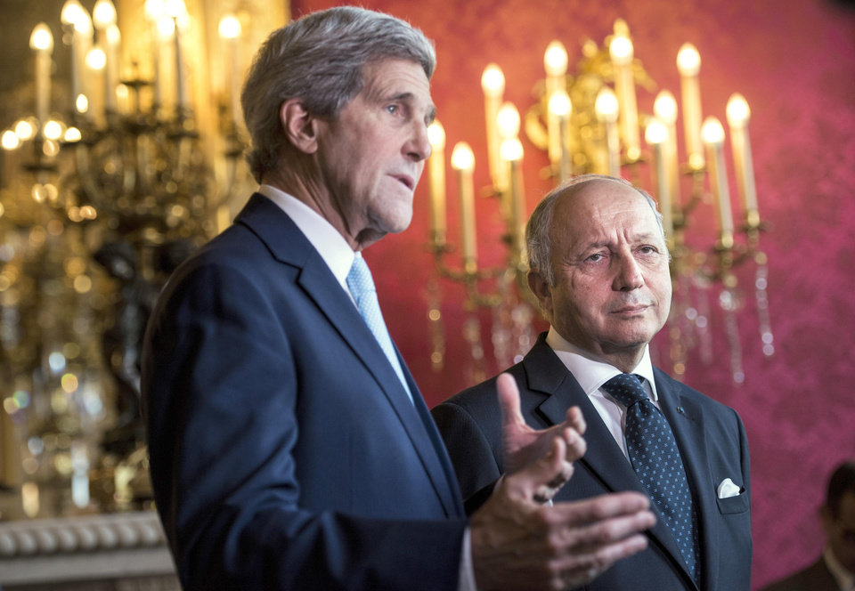 Photo - French Foreign Affairs Minister Laurent Fabius, right, listens as US Secretary of State John Kerry makes statements to the press after their meeting at the 'Quai d'Orsay' Foreign Affairs Ministry in Paris, France, Thursday, June 26, 2014. US Secretary of State John Kerry arrived in Paris on June 26, 2014 after stops in Baghdad, Arbil and Brussels to brief his Saudi, French and Israeli counterparts on his talks in Iraq and discuss the bloody three-year war in Syria. (AP Photo/Brendan Smialowski, pool)