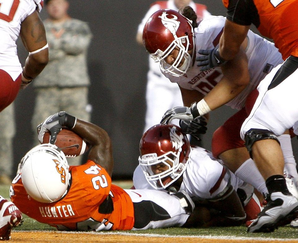 Photo - OSU's Kendall Hunter (24) scores a touchdown as WSU's Tyree Toomer, bottom, and Bernard Wolfgramm tackle him during the college football game between the Washington State Cougars (WSU) and the Oklahoma State Cowboys (OSU) at Boone Pickens Stadium in Stillwater, Okla., Saturday, September 4, 2010. Photo by Sarah Phipps, The Oklahoman