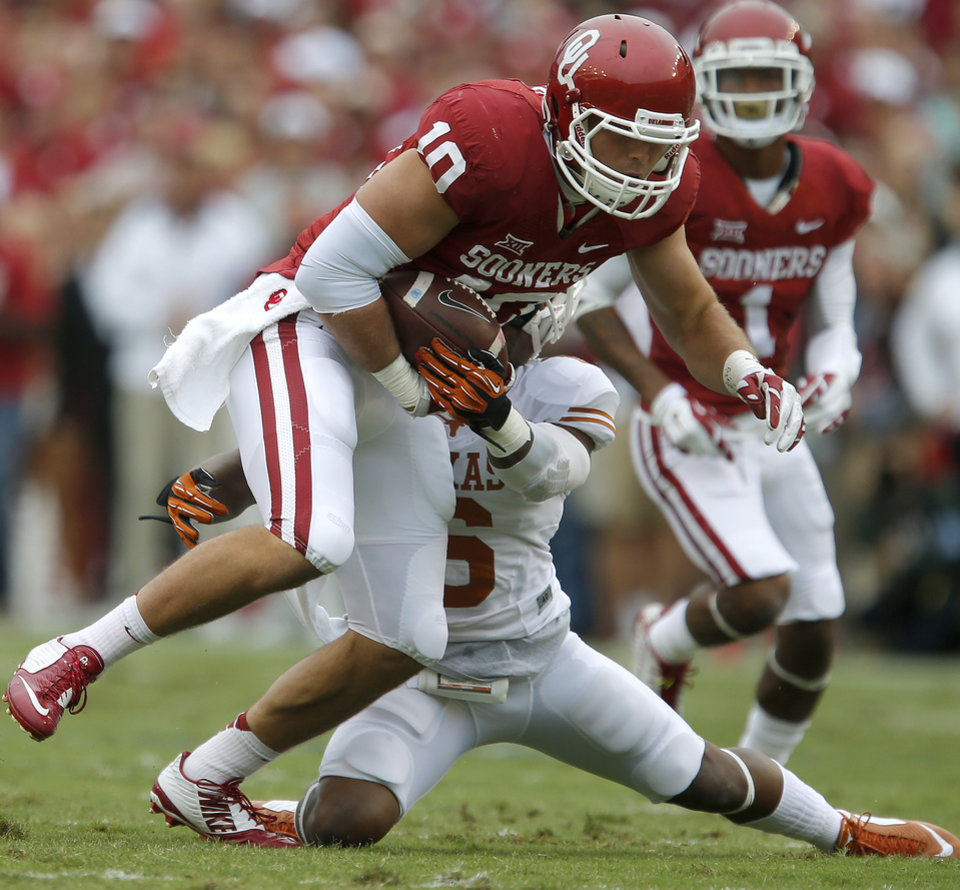 Photo - Oklahoma's Blake Bell (10) tries to get past Texas' Quandre Diggs (6) during the Red River Showdown college football game between the University of Oklahoma Sooners (OU) and the University of Texas Longhorns (UT) at the Cotton Bowl in Dallas on Saturday, Oct. 11, 2014. 