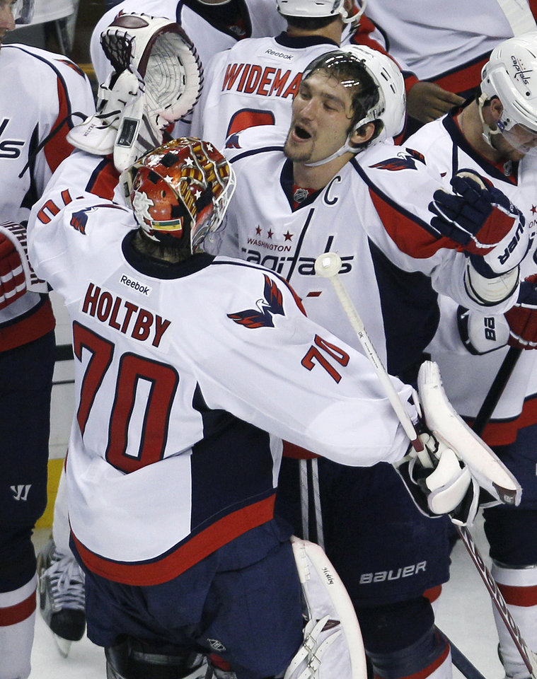 Photo -   Washington Capitals goalie Braden Holtby (70) celebrates with teammate Alex Ovechkin after the Capitals' 2-1 win over the Boston Bruins in overtime in Game 7 of an NHL hockey Stanley Cup first-round playoff series, in Boston on Wednesday, April 25, 2012. (AP Photo/Charles Krupa)