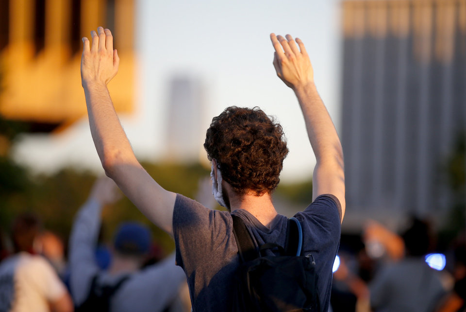Photo - A person raises their hands in the air as they march during a protest near the intersection of 23rd and Classen in Oklahoma City, Saturday, May 30, 2020. The protest was in response to the death of George Floyd. [Sarah Phipps/The Oklahoman]