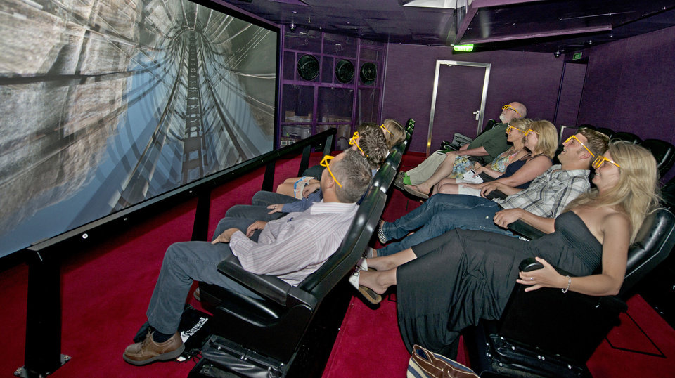 In this June 17, 2012 photo provided by Carnival Cruise Lines, guests onboard Carnival Breeze enjoy the Thrill Theater, an interactive, multi-dimensional experience that makes them feel as if they are part of the movie. Among various sensory effects, seats shift back and forth, move from side to side and also vibrate, creating an exciting and exhilarating experience. (AP Photo/Carnival Cruise Lines, Andy Newman)