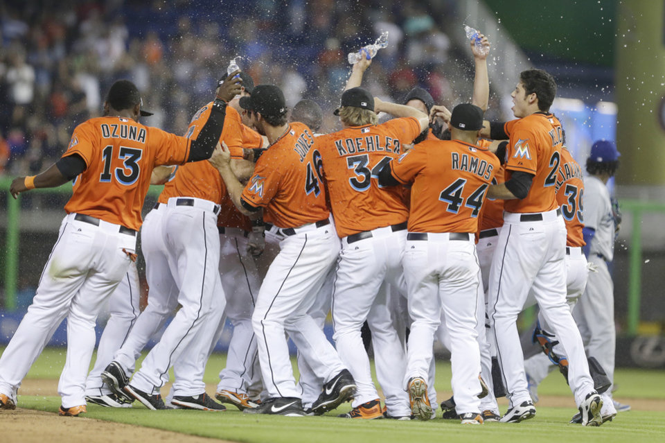 Photo - Miami Marlins players mob Jeff Baker, after he hit a double that scored Adeiny Hechavarria, during the ninth inning of a baseball game against the Los Angeles Dodgers, Sunday, May 4, 2014 in Miami. The Marlins defeated the Dodgers 5-4. (AP Photo/Wilfredo Lee)